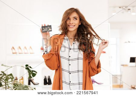 Portrait of an excited woman holding credit card while shopping at a shoe boutique