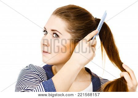Woman combing her healthy hair using comb. Young latin female with beautiful natural brown straight long hairs, studio shot isolated on white