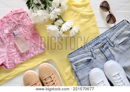 Womens fashion clothing, shoes (white leather sneakers, blue jeans, yellow top (long sleeve t-shirt). Wish list or shopping overview, fashion concept. View from above, Flat lay. Trending. Spring summer season