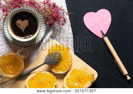 Breakfast with coffee and heart shape paper note - Romantic breakfast with flowers, heart shaped sticky note, bread with jam on a trencher and a cup of coffee with a foam heart, on a black table.