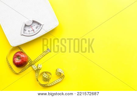 Lose weight concept. Scale and measuring tape on yellow background top view.