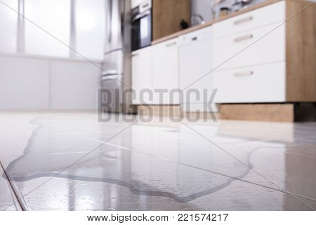 Close-up Of Spilled Water On Kitchen Floor At Home