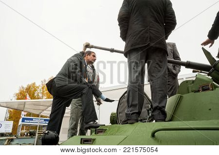 Nizhniy Tagil, Russia - September 27. 2013: Russia Arms Expo-2013 exhibition. Representatives of JSC Military-industrial Company communicate with foreign delegation members on tank