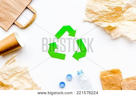 Green paper recycling sign among waste materials paper, plastic, polyethylene on white background top view.