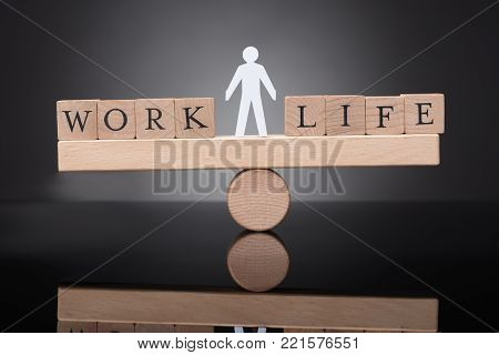 Human Figure Balancing Between Work And Life On Wooden Seesaw Against Black Background