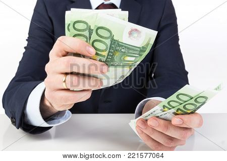 Businessman's hand holding money, euro banknotes. Financials, investment success and profitable business concept.