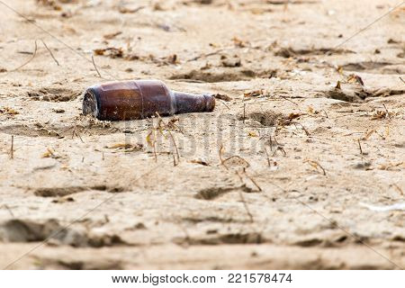 glass bottle in the sand . In the park in nature