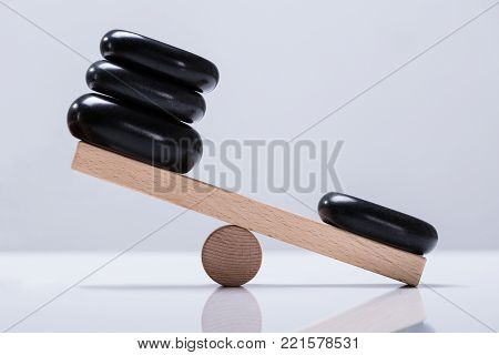 Black Stones Balancing On Wooden Seesaw Over The White Background