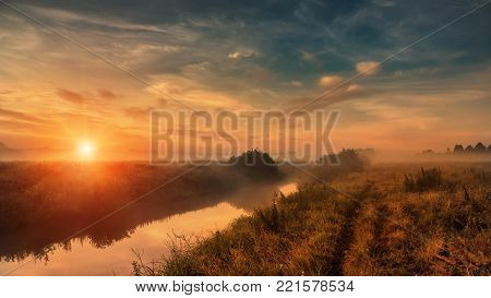 wonderful dramatic scene. fantastic foggy sunrise over the meadow with colorful clouds on the sky. picturesque rural landscape, misty morning. color in nature. beauty in the world