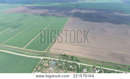 Fields in the Kuban view from a height. Young wheat and plowed field a little further from the village. The flight over a field of winter wheat. Fields cereals, top view.
