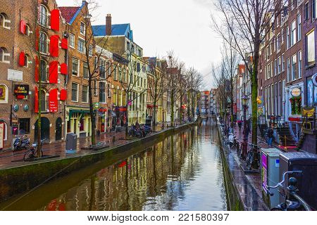 Amsterdam, Netherlands - December 14, 2017: The people going near most famous canal and embankment at Amsterdam, Netherlands on December 14, 2017. General view of the cityscape and traditional Netherlands architecture