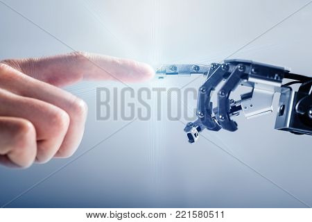 Close-up Of Businessperson's Finger Touching Robotic Finger On Blue Background