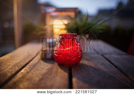 red glass candlestick on a table in a street cafe