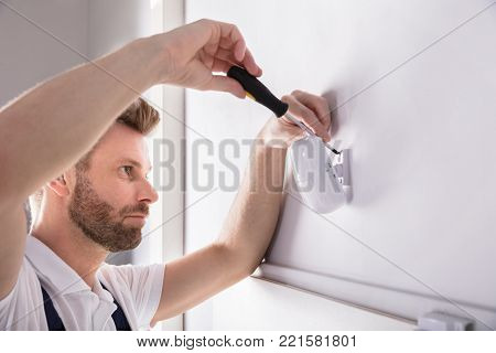 Young Male Technician Installing Security System Door Sensor With Screwdriver