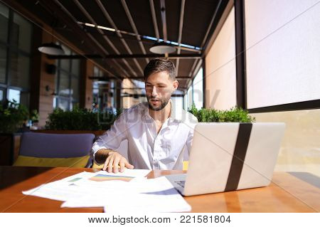 European businessman working at table with laptop and reading documents. Successful man dressed in white shirt has beard. Concept of using fast internet and modern technologies for biz.