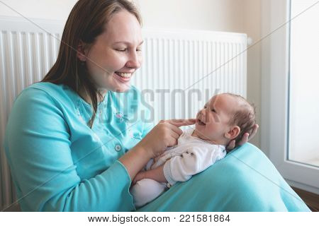 Happy Mother And Her Newborn Smiling Baby