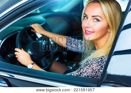 Happy smiling young blond woman in the modern luxury car