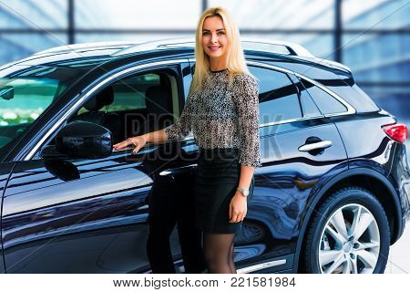 Young happy smiling blond woman sdriver tanding in front of a new luxury car in the dealer showroom