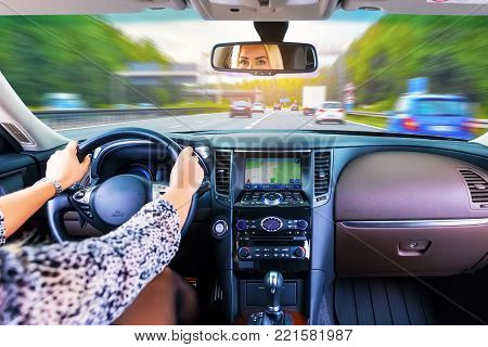 Young business woman driver driving a car on a highway