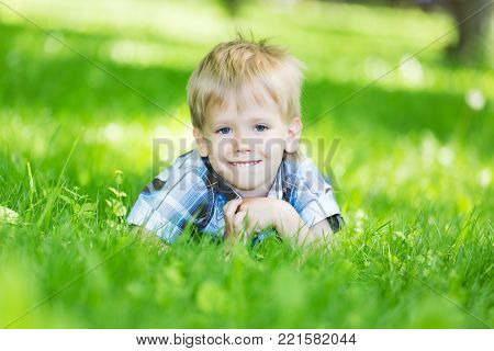 Portrait of a little boy laying on the fresh grass loan in the city park in summer