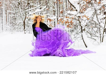 Young beautiful blond woman in a long purple dress in the snowy winter forest or wood outdoors