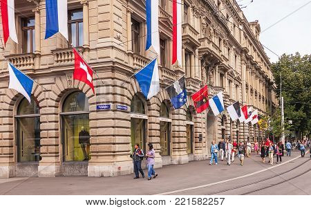 Zurich, Switzerland - 1 August, 2014: buildings on Paradeplatz square and Bahnhofstrasse street decorated with flags for the Swiss National Day, people passing along the street. The Swiss National Day is the national holiday of Switzerland.