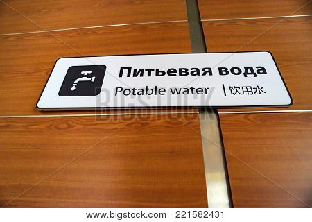 Close up plae with potable water icon on wooden background in airport