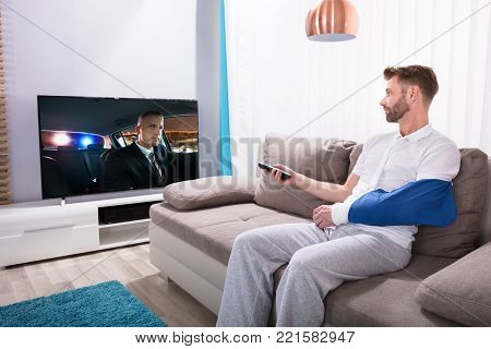 Young Man With Fractured Hand Sitting On Sofa Watching Movie On Television At Home