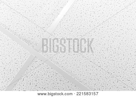 The texture with  ceiling rails. Frontal view. Suspended ceiling white styrofoam plate texture bark beetle.