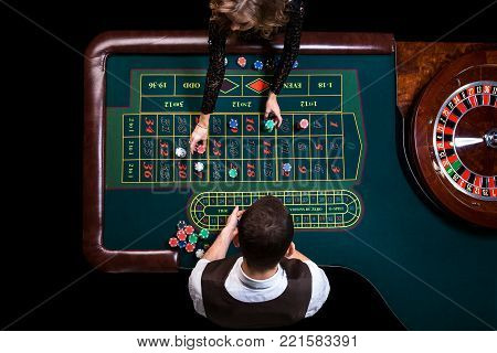 Gambling table in luxury casino. Top view of the casino croupier and the green roulette table. Gambling. Casino. Roulette. Poker.
