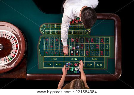 Man croupier and woman playing roulette at the table in the casino. Top view at a roulette green table with a tape measure. Table for gambling in a luxury casino. Gambling. Casino roulette