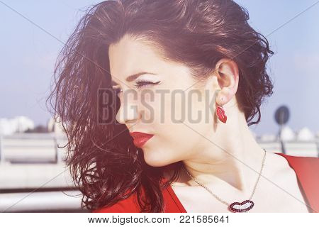 Portrait of a glamorous pretty girl with long red hair. A pretty woman posing on a background of a summer nature. Female street fashion style. Beautiful elegant pretty model