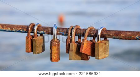 Rusty padlocks locks on peeled railing. Tradition for couple in love. Blur backdrop, closeup, detail