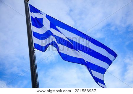 Waving flag of Greece on flagpole. Blue sky with few clouds backdrop.