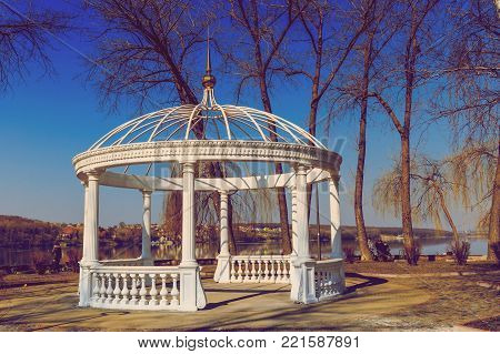 bewitching spring morning. beautiful white gazebo by the lake. in a city park. beauty in the world. toning