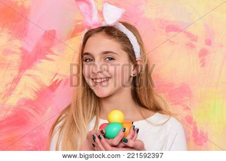 colorful painted easter eggs as traditional spring holiday food. happy girl in pink bunny ears with long blonde hair and adorable smiling face on abstract background