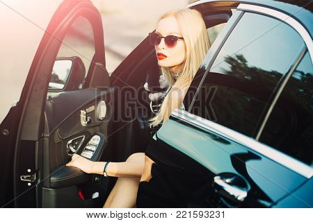 Travel and vacation. Modern life, luxury, city, glamour. Business trip or commanding, call girl. Businesswoman or pretty blonde girl with red lips in car. Young woman get out of car with sexy leg.