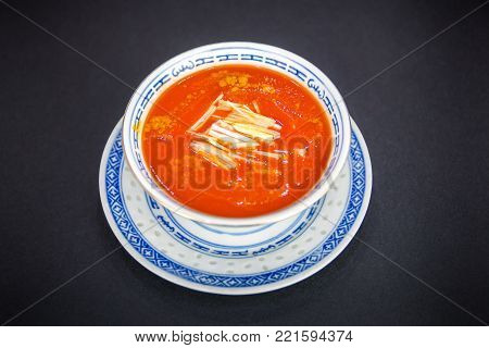 Chinese food. Vermicelli spicy red hot soup with tomato and eggs in porcelain bowl on black background.