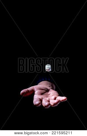 hand tosses a die for good luck on a black background