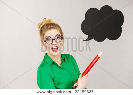Student looking woman wearing nerdy eyeglasses holding big oversized pencil thinking about something, black speech bubble next to her