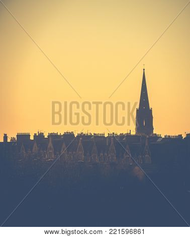 Retro Style Image Of A Row Of Edinburgh Tenement Apartments And Church Spire At Sunset