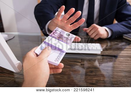 Cropped Hand Of Businessperson Refusing To Take Bribe From Partner At Workplace