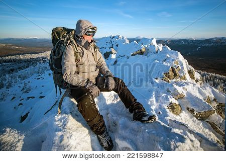 Hiker with backpack sitting and having rest on the top of a snow-covered rock over the winter mountains.