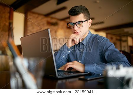 Thoughtful young caucasian businessman in glasses working on laptop computer. Pensive attractive hipster freelancer thinks over the solution of the problem with computer in cafe.