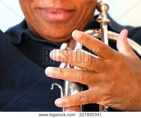 African american jazz musician expressions with his flugelhorn.