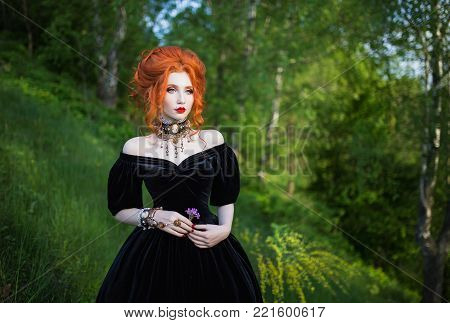 Unusual woman is a vampire with pale skin and red hair in a black unusual dress and a necklace on her neck against the background of nature. Unusual girl witch with vampire claws and red lips. Unusual gothic look.