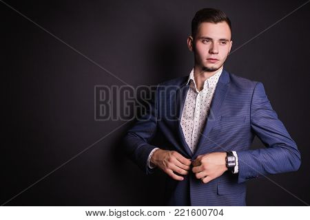Successful business man in business suit and shirt and fashionable clock. Stylish business man in jacket. Business man in suit button up his buttons. Business concept. Business meeting. Conceptual picture of a business man in suit