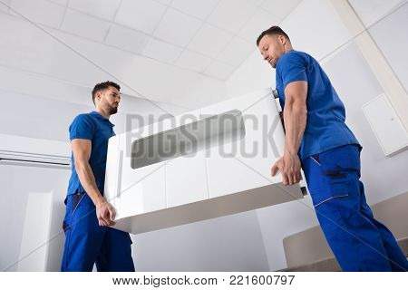 Two Smiling Young Male Movers Holding Furniture In Living Room