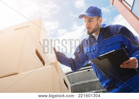 Low Section Of Young Male Worker Standing Near Cardboard Box Holding Clipboard
