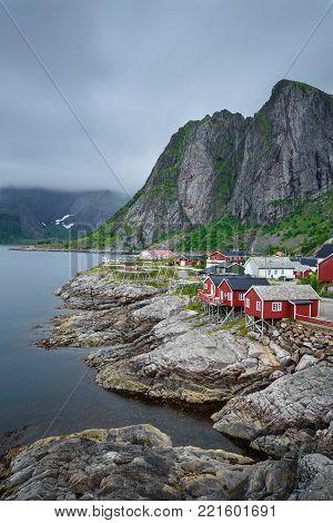 Traditional red rorbu cottages under the  Lilandstinden mountain peak in Hamnoy village, Lofoten islands, Norway. Long exposure.